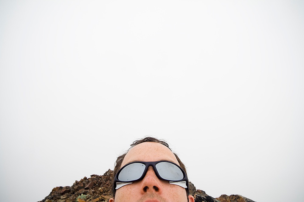 Brian Polagye rests on the summit of Tomyhoi Peak in a complete whiteout, Mount Baker Wilderness, Washington.