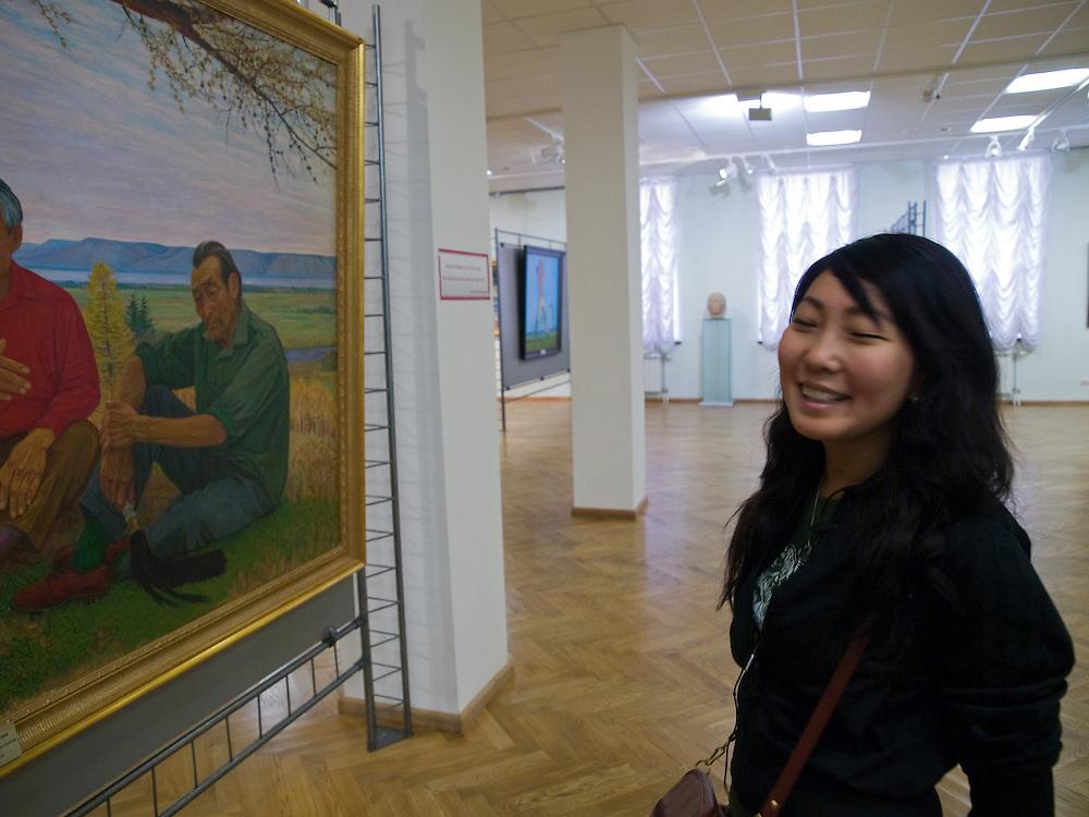 Besucherin vor Gemaelden im nationalen Kunstmuseum der Teilrepublik Sacha (Jakutien) im Zentrum von Jakutsk. Jakutsk hat 236.000 Einwohner (2005) und ist Hauptstadt der Teilrepublik Sacha (auch Jakutien genannt) im Foederationskreis Russisch-Fernost und liegt am Fluss Lena. Jakutsk ist im Winter eine der kaeltesten Grossstaedte weltweit mit durchschnittlichen Winter Temperaturen von -40.9 Grad Celsius.<br /> <br /> Visitor infront of paintings at The National Art Museum of Sakha Republic (Yakutia) in the center of Yakutsk. Yakutsk is a city in the Russian Far East, located about 4 degrees (450 km) below the Arctic Circle. It is the capital of the Sakha (Yakutia) Republic (formerly the Yakut Autonomous Soviet Socialist Republic), Russia and a major port on the Lena River. Yakutsk is one of the coldest cities on earth, with winter temperatures averaging -40.9 degrees Celsius.