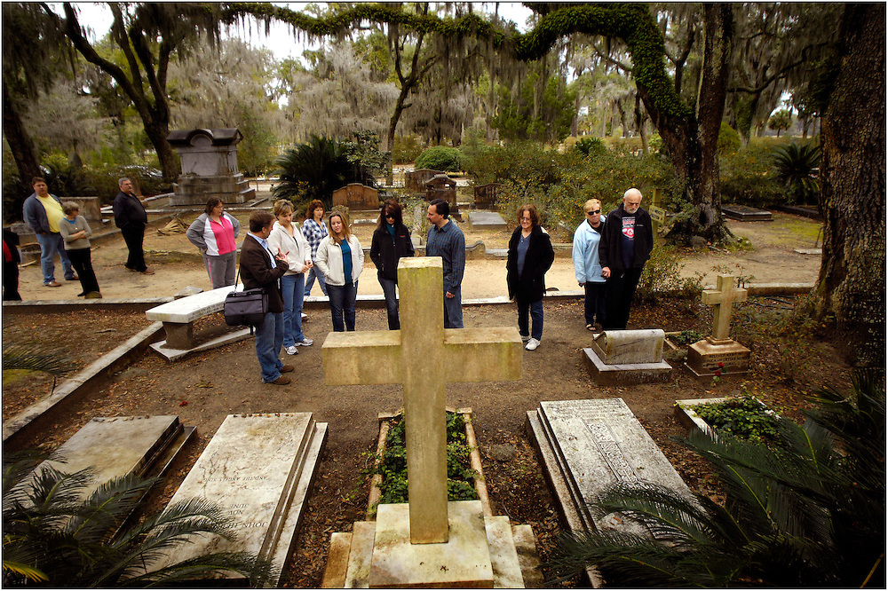 Historic narrator Larry Rockwell, left, speaks to a group of tourist about the grave of legendary song writer Johnny Mercer while standing in the family burial plot at Bonaventure Cemetery Sunday January 24, 2010 in Savannah Georgia. Mercer's grave, second from the bottom left,  is a popular stop for visitors in the historic cemetery. (Stephen Morton for The New York Times).....