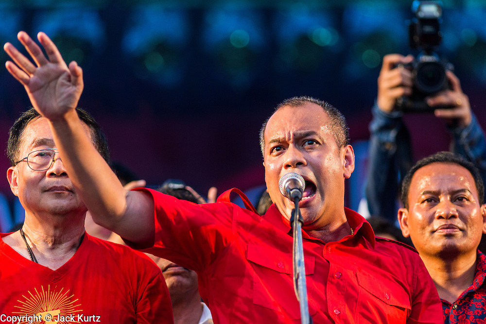 10 MAY 2014 - BANGKOK, THAILAND: NATTAWUT SAIKUA, a leader of the Red Shirt movement, speaks to Red Shirts at a Red Shirt rally in Bangkok. Thousands of Thai Red Shirts, members of the United Front for Democracy Against Dictatorship (UDD), members of the ruling Pheu Thai party and supporters of the government of ousted Prime Minister Yingluck Shinawatra are rallying on Aksa Road in the Bangkok suburbs. The government was ousted by a court ruling earlier in the week that deposed Yingluck because the judges said she acted unconstitutionally in a personnel matter early in her administration. Thailand now has no functioning government. Red Shirt leaders said at the rally Saturday that any attempt to impose an unelected government on Thailand could spark a civil war. This is the third consecutive popularly elected UDD supported government ousted by the courts in less than 10 years.    PHOTO BY JACK KURTZ