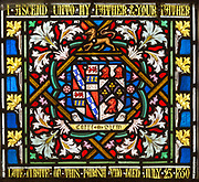Detail of stained glass window with flowers and floral and Coat of Arms decoration, All Saints church, Stanton St Bernard, Wiltshire circa 1850 Carpe Diem inscription