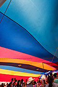 Crowds gather under a colorful tarp to eat a a food stall at the Tuesday Market in San Miguel de Allende, Guanajuato, Mexico.