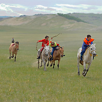MONTOLIAN NAADAM FESTIVAL. Young, costumed bareback riders approach end of a 20km race at a traditional naadam festival on a remote pass in Arbulag Sum, near Muren in Hovsgol Aimag, Mongolia.