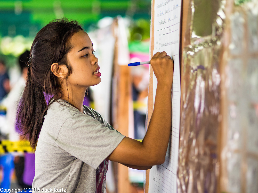 07 AUGUST 2016 - BANGKOK, THAILAND: An elections worker writes down the referendum tally in a polling place in Bangkok Sunday. Thais voted Sunday in the referendum to approve a new charter (constitution) for Thailand. The new charter was written by a government appointed panel after the military coup that deposed the elected civilian government in May, 2014. The charter referendum is the first country wide election since the coup. Elections workers counted the votes in the polling places after the polls closed at 16.00.      PHOTO BY JACK KURTZ