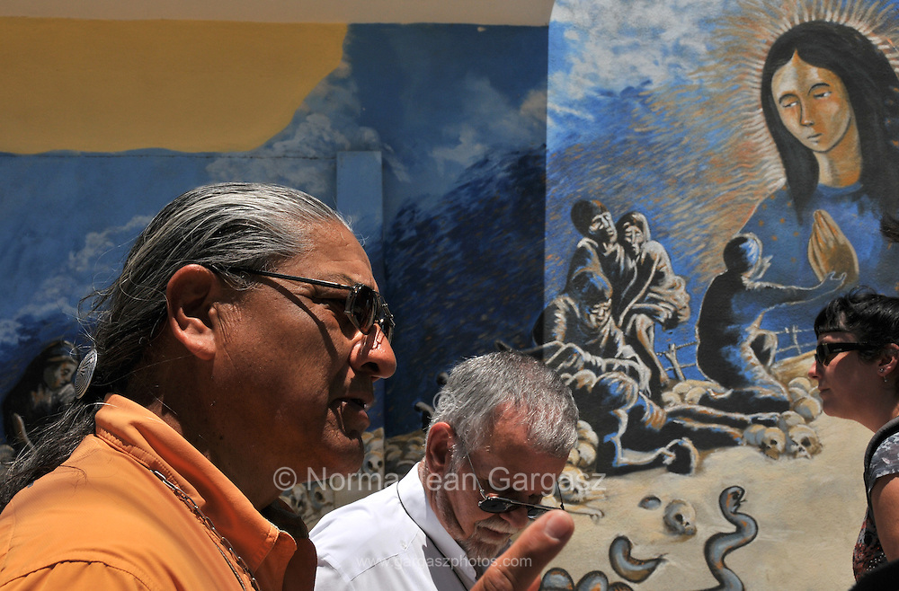 Border activists Rev. Mike Wilson, (left), and Rev. Robin Hoover of Tucson, Arizona, USA, walk in Altar, Sonora, Mexico, near a mural that depicts the journey crossing the border from Mexico in to the Arizona desert.  Hoover established a migrant safety initiative, Project Rescue Me!  Proyecto Rescatame!, which distributes GPS devices to migrants and guides.  Wilson distributes water along the migrant trails in the Arizona desert.