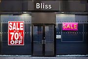 Street view of Bliss shop front in Middlesborough town centre, North Yorkshire, United Kingdom.  The shop is currently closed and has the shutters down, but the  windows display its sale signs.