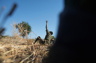 An SPLA-North soldier points up at a bomber outside of Kadulguli.