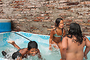 Children play in a pool in the backyard of a house at Ocho de Mayo.