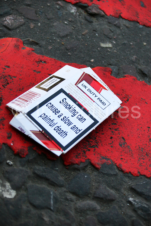 """Health warning against smoking on a crushed packet of cigarettes on a red route line. The warning says """"Smoking can cause a slow and painful death""""."""