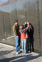 Washington DC; USA: The Vietnam Veterans Memorial on the Mall.  Two people look at a name on the wall..Photo copyright Lee Foster Photo # 8-washdc76102