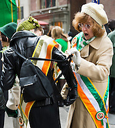 March 16, 2013 - New York, NY, U.S. - Woman helpis fellow marcher untangle her backpack straps from orange, green, and white sash, shortly before they march in the 252nd annual NYC St. Patrick's Day Parade.