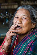 An elderly Gurung woman smokes a cigarette in her kitchen in the Annapurna Himalaya, Nepal.