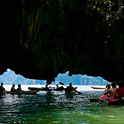 People in kayaks under the limestone cliffs of the Phang Nga Bay caves, Thailand