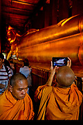 Monk using ipad or tablet computer to photograph the Reclining Buddha. Wat Pho is one of the largest and oldest wats in Bangkok (with an area of 50 rai, 80,000 square metres), and is home to more than one thousand Buddha images, as well as one of the largest single Buddha images of 160 ft length: the Reclining Buddha .