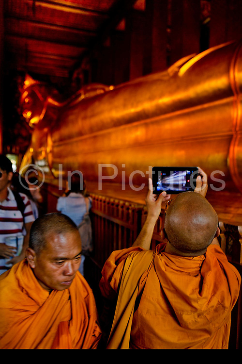 Monk using ipad or tablet computer to photograph the Reclining Buddha. Wat Pho is one of the largest and oldest wats in Bangkok (with an area of 50 rai, 80,000 square metres), and is home to more than one thousand Buddha images, as well as one of the largest single Buddha images of 160ft length: the Reclining Buddha .