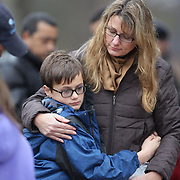 Kady Vales hugs her son Mason, 10, while paying their respects at the shrine set up around the towns Christmas tree in Sandy Hook after the mass shootings at Sandy Hook Elementary School, Newtown, Connecticut, USA. 16th December 2012. Photo Tim Clayton