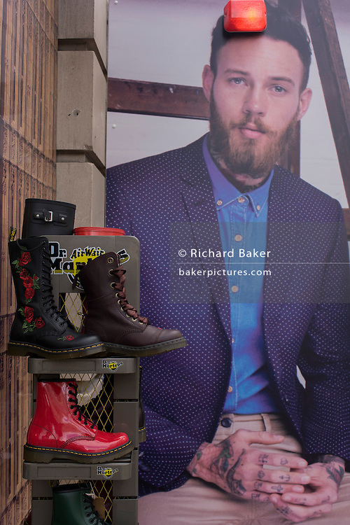 Dr Martens boots and construction hoarding featuring suited young man for dress hire business Moss Bros in central London.