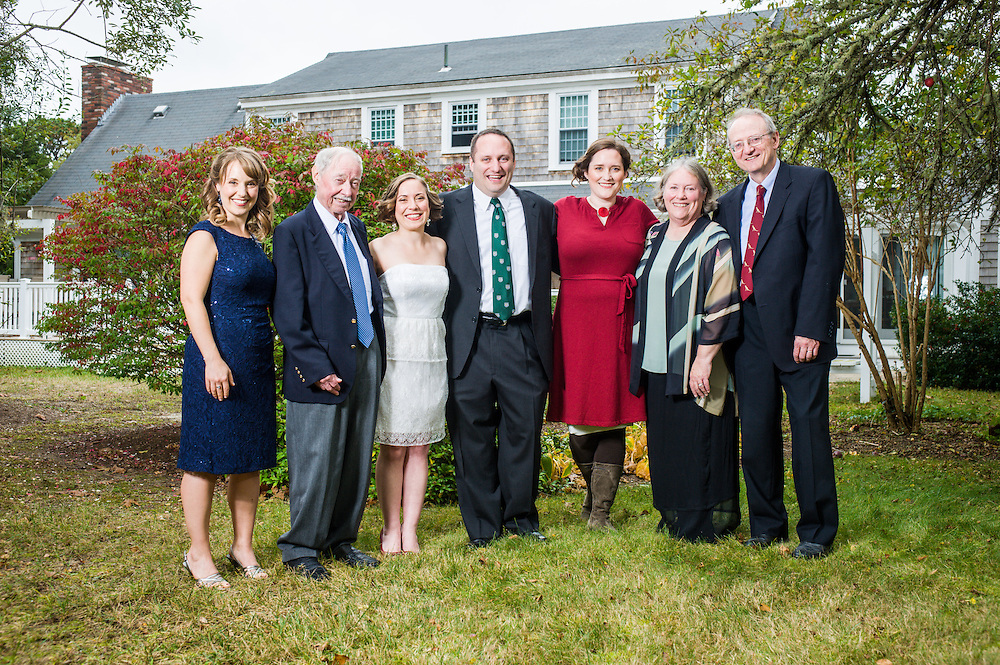 A bride and groom with their family in the backyard before their wedding in Chatham, MA.