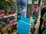 11 OCTOBER 2015 - BANGKOK, THAILAND:  A snack vendor goes shop to shop in Saphan Lek market on what Bangkok city officials say is the last day of business for the market. Many shops in the market are already closed. Street vendors and illegal market vendors in the Saphan Lek area will be removed in the next two weeks as a part of an urban renewal project coordinated by the Bangkok Metropolitan Administration. About 500 vendors along Damrongsathit Bridge, popularly known as Saphan Lek, have until Monday, October 11,  to relocate. Vendors who don't move will be evicted. Saphan Lek is one of several markets and street vending areas being closed in Bangkok this year. The market is known for toy and replica guns, bootleg and pirated DVDs and CDs and electronic toys.   PHOTO BY JACK KURTZ
