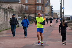 Portobello, Scotland, UK. 28 March, 2020. On the first weekend of the coronavirus lockdown the public were outdoors exercising and maintaining social distancing along Portobello beachfront promenade. Pictured, People walking and jogging on the promenade. Iain Masterton/Alamy Live News