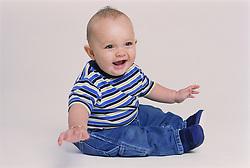 Portrait of baby boy sitting down wearing copper bracelet,