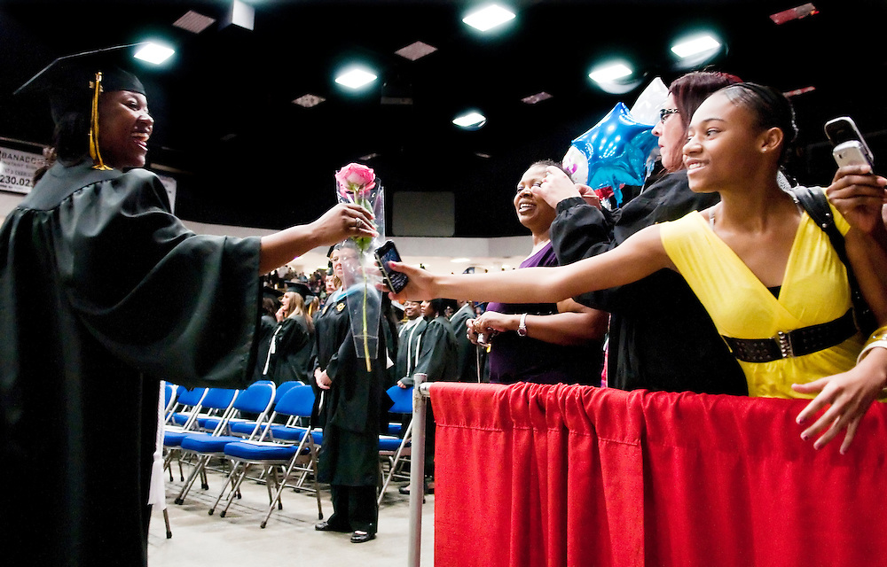 Matt Dixon | The Flint Journal..Mott Community College graduate Kara Morris, 32, of Flint, receives a flower from her daughter Kara during the ceremony held at the Perani Arena Saturday afternoon. Morris graduated with a degree in social work.