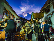 11 OCTOBER 2016 - UBUD, BALI, INDONESIA:  People shop and walk through the market in Ubud just before sunrise. The morning market in Ubud is for produce and meat and serves local people from about 4:30 AM until about 7:30 AM. As the morning progresses the local vendors pack up and leave and vendors selling tourist curios move in. By about 8:30 AM the market is mostly a tourist market selling curios to tourists. Ubud is Bali's art and cultural center.     PHOTO BY JACK KURTZ