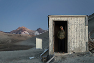 A backpacker stands in the doorway of a small hut on Baked Mountain in the Valley of Ten Thousand Smokes, Katmai National Park, Alaska