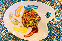 """Kawai Monster Cafe Multicolored Pasta  - Steven King says that monsters are real and live inside us.  The Kawai Monster Cafe is a perfect place to test this theory out. The cafe is right at home in Harajuku, which has quite a few monsters in the neighborhood.  And cuteness.  Kawai Monster Cafe is not about the cuisine, which has not been reviewed kindly.  It's all about the presentation and the decor that keep customers coming.  The place has differently themed areas, though the Mushroom Disco is probably the most colorful.  In an adjacent area you'll find the Milk Stand which features milk bottle lights and a cracked mirror ceiling to add to the trippy look.  The mascot is """"Choppy"""" or Mr. Ten Thousand Chopsticks.  Another highlight is a kind of cake-merry-go-round called Sweets-go-Round.  The Bar Experiment is meant to resemble a giant jellyfish complete with illuminated sea creatures.  The rest rooms are also kitted out in color.  Even if mother nature doesn't call, it is worth visiting anyway just for the unique experience and decor."""