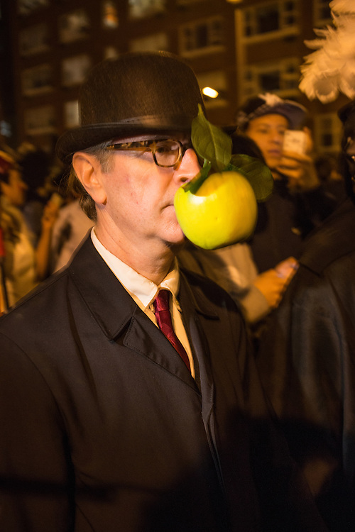 New York, NY, October 31, 2013. A man in a bowler hat with a green apple stuck to the front of his face referenceing a painting by Rene Magritte in the Greenwich Village Halloween Parade.