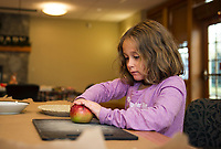 Delaney cuts up apples for her apple pie during Gilford Library's pie making activity on Tuesday afternoon.  (Karen Bobotas/for the Laconia Daily Sun)