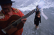 """Europe, France, Camargue, Saintes Maries de la Mer. A Manouche Gypsy father plays guitar,  with his daughter in the surf after the procession. The Gypsy festival """"le Pelerinage des Gitans aux Saintes Maries de la Mer"""" takes place every year in mid May. Gypsies arrive from all over Europe a few weeks before the main festival days, the 24th and 25th May.  The pilgrimmage is Catholic but many Gypsies, Manouche, Gitans, Roma come to see their patron 'Saint Sara' and for the festival atmosphere, the yearly gathering of friends, the music and dance. Gypsies are still regarded with much distrust and racism, they are not liked by the shopkeepers but are well treated by the gentry, especially the Baroncelli family who were instrumental in making this officially a Gypsy festival. One Hundred years ago the Gypsies were not allowed into the church, as it is they still have to camp outside the town."""