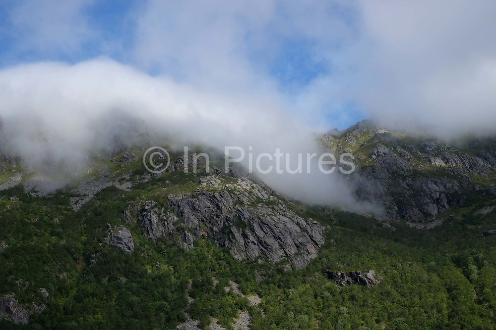 Low clouds over the mountains on 22nd August 2016 on the Lofoten Islands, Norway. The Lofoten islands are famous for their jagged mountains, red-painted rorbu cabins and racks with fish hanging closely packed to dry.