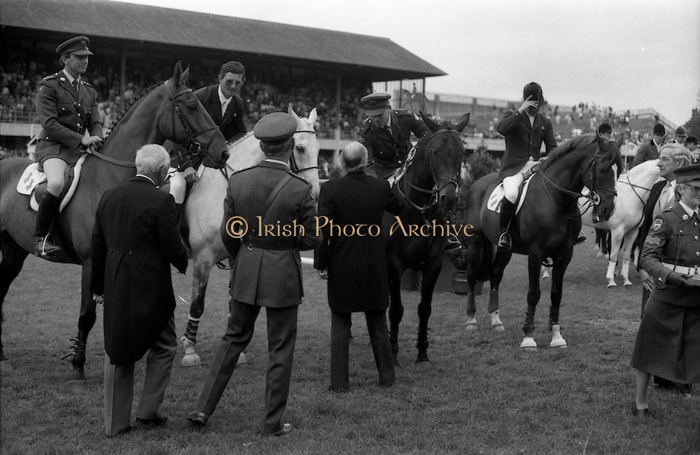 """07/08/1987<br /> 08/07/1987<br /> 07 August 1987<br /> Bank of Irelands Nations Cup for the Aga Khan trophy competition at the Dublin Horse Show at the RDS, Dublin. President Hillery congratulating Commandant Gerry Mullins, on """"Limerick"""" on Ireland's win in the Bank of Ireland Nation's Cup.  Also pictured are: (mounted l-r) Captain John Ledingham on """"Gabhran""""; Jack Doyle on """"Hardly"""" and Eddie Macken on """"Carroll's Flight""""."""