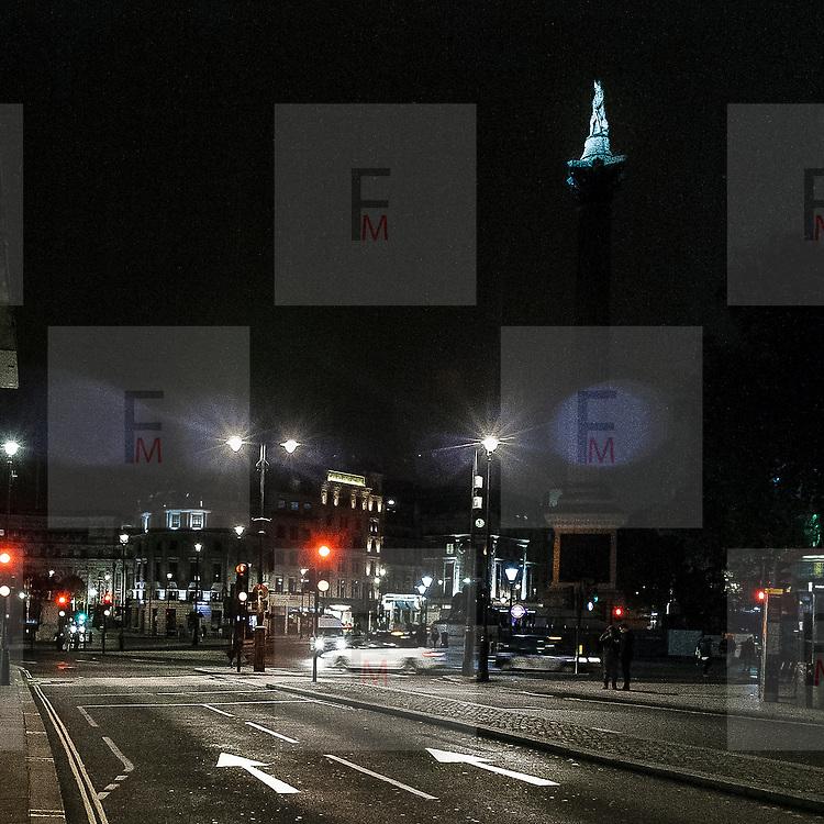 Trafalgar Square con la statua dell'ammiraglio Nelson che controlla il traffico.<br /> <br /> Trafalgar Square and the statue of Admiral Nelson that is checking the nocturne traffic.