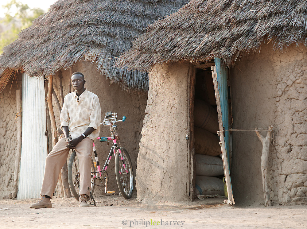 Man of the Nuba tribe sitting on his bicycle outside a storage hut in the village of Nyaro, Kordofan region,