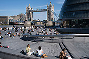 People enjoying some sunny weather socialising at The Scoop at More London and overlooking the Tower Bridge and City Hall on 17th April 2021 in London, United Kingdom.