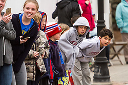 young race fans await passing runners