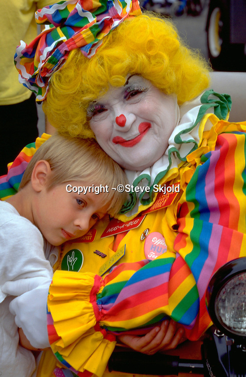 Clown age 55 holding child age 7 at West End Parade.  St Paul  Minnesota USA