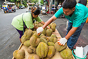 27 APRIL 2013 - BANGKOK, THAILAND:   A couple sets up their durian stand (durian a Thai fruit) in Talat Noi. The Talat Noi neighborhood in Bangkok started as a blacksmith's quarter. As cars and buses replaced horse and buggy, the blacksmiths became mechanics and now the area is lined with car mechanics' shops. It is one the last neighborhoods in Bangkok that still has some original shophouses and pre World War II architecture. It is also home to a  Teo Chew Chinese emigrant community.         PHOTO BY JACK KURTZ