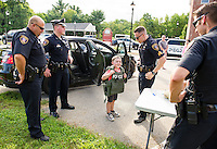 Lt. Richard Mann, Ofc. Patrick Riley, Sgt. Adam Hawkins, and Ofc. Kris Kloetz watch as Owen Hawkins tries on a Swat team vest weighing 12 lbs. during Belmont's National Night Out on Tuesday evening.  (Karen Bobotas/for the Laconia Daily Sun)