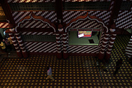 """Inside the Jami Ul-Alfar Mosque in Colombo, Sri Lanka, a man walks past a digital display that reads, """"Purchase a ticket @ RS5,500/= to build a square feet of masjid and gain a place in Paradise.""""  (March 31, 2017)"""
