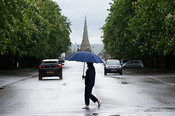 © Licensed to London News Pictures 13/05/2021.  Greenwich, UK. A woman in the park under her umbrella. People out and about in Greenwich Park, London on a cold and rainy day today.  Photo credit:Grant Falvey/LNP