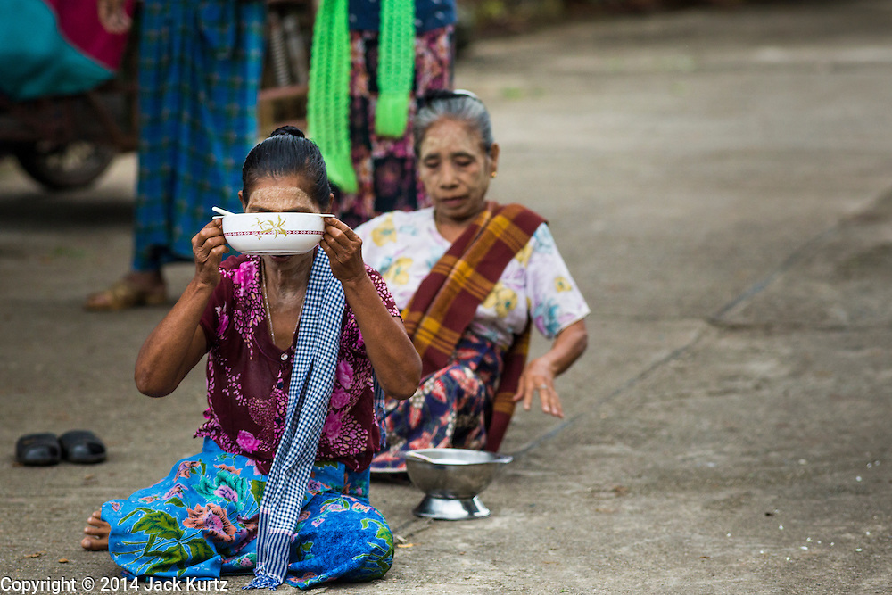 16 SEPTEMBER 2014 - SANGKHLA BURI, KANCHANABURI, THAILAND: Burmese Mon women sit in the road and pray before making merit and present Mon Buddhist monks with food during the morning alms round in the Mon community in Sangkhla Buri. The Mon were some of the first people to settle in Southeast Asia, and were responsible for the spread of Theravada Buddhism in Thailand and  Indochina. The Mon homeland is in southwestern Thailand and southeastern Myanmar (Burma). The Mon in Thailand traditionally allied themselves with the Thais during the frequent wars between Burmese and Siamese Empires in the 16th - 19th centuries and the Mon in Thailand have been assimilated into Thai culture. The Mon in Myanmar were persecuted by the Burmese government and many fled to Thailand. Sangkhla Buri is the center of Burmese Mon culture in Thailand because thousands of Mon came to this part of Thailand during the persecution.    PHOTO BY JACK KURTZ