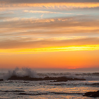 Sunset illuminates waves washing ashore on the California Coast near Moss Beach.