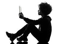 one mixed race african young teenager girl woman using digital tablet  in studio shadow silhouette isolated on white background