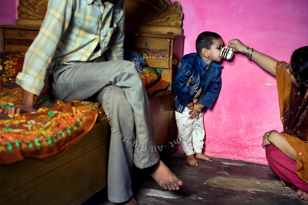 Riswana, 25, (left) is offering Indian chai tea to his disabled son Maheraj, 2 and a half years old, while sitting near her husband Mahfus Ali, 32, (left) a gas survivor, inside their home in Model Ground, Bhopal, Madhya Pradesh, central India, site of the infamous 1984 gas tragedy. The poisonous cloud that enveloped Bhopal left everlasting consequences that today continue to consume people's lives. A few years ago Mahfus Ali and his wife Riswana, 25, lost a child facing similar health problems to those of Maharaj. The boy survived only a few days and was born with severe birth defects. Salya, 4, a girl, is the parents's only healthy child.