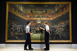 """© Licensed to London News Pictures. 27/09/2019. LONDON, UK. Technicians present """"Devolved Parliament"""", 2009, by Bansky (Est. GBP1.5-2m). Preview of Sotheby's Frieze Week Contemporary Art exhibition at its New Bond Street galleries.  Over 250 works by artists, including Andy Warhol, David Hockney and Jean-Michel Basquiat, will be auctioned on 3 October 2019.  Photo credit: Stephen Chung/LNP"""
