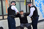 An enviroment protester is arrested in front of the entrance of Shell oil HQ on 15th April 2019 in London, United Kingdom.  Extinction Rebellion a climate change protest group are protesting  across the centre of London and plan to block traffic for the next five days.