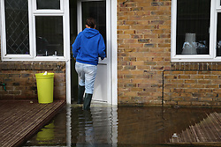 © Licensed to London News Pictures. 24/02/2014. Basingstoke, Hampshire, UK. Kirsty Campbell (23) entering her house on Sperrin Close which she and her family have had to evacuate due to groundwater flooding in the Buckskin area of Basingstoke, Hampshire. Groundwater levels are continuing to rise in the area, forcing 69 homes to be evacuated in the Buckskin Area of the commuter town. Photo credit : Rob Arnold/LNP